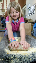 Paul Fraughton | Salt Lake Tribune Mary Emmaline Hansen, 8, tries grinding corn using a mano and matate ( ancient stone tools) at the archaeology open house Saturday at the Utah State History Museum at the Rio Grande Depot. The event  was part of Archaeology Week activities that began Saturday and will run through May 12th. At the open house, children participated in hands on activities with a  archaeological theme.