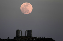 The full moon rises behind the Temple of Poseidon in Cape Sounion, south east of Athens, Greece, while tourists watch, on Saturday, May 5, 2012.  Saturday's event is a