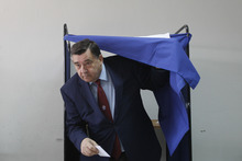 ADDS NAME OF LEADER OF LAOS PARTY  Leader of the rightwing LAOS party George Karatzaferis opens the screen to a polling booth at a polling station in Athens, Sunday, May 6, 2012. Greeks cast ballots on Sunday in their most critical _ and uncertain _ election in decades, with voters set to punish the two main parties that are being held responsible for the country's dire economic straits. (AP Photo/Kostas Tsironis)
