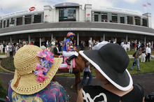 Race goers watch as jockey Colm O'Donoghue rides Revolving through the paddock before the third race at the 138th Kentucky Derby horse race at Churchill Downs Saturday, May 5, 2012, in Louisville, Ky. (AP Photo/Mark Humphrey)