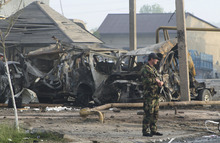 A police officer guards the site of a powerful explosion on the outskirts of Makhachkala, southern Russia, Friday, May 4, 2012. Two powerful explosions went off Thursday night near a traffic police post in the capital of Russia's restive Dagestan region. (AP Photo/Abdula Magomedov, NewsTeam)