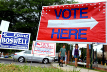 Signs are displayed at the First Presbyterian Church in Burlington, N.C., on Tuesday May 8, 2012, as people approach the building to cast their ballots. North Carolina could be the next state to pass a constitutional amendment defining marriage as solely between a man and a woman. Voters are casting their ballots Tuesday. (AP Photo/Burlington Times-News, Sam Roberts)