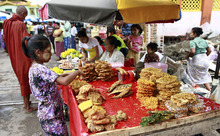 A food vendor prepares snacks for visitors for the full-moon day of Kasone, the second month of Myanmar Calendar, at Potataung Pagoda, in Yangon, Myanmar, Saturday, May 5, 2012. (AP Photo/Khin Maung Win)
