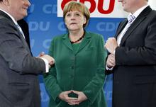 German Chancellor Angela Merkel, center, chats at the beginning of a board meeting of the German Christian Democratic party in Berlin, Germany, Monday, May 7, 2012. (AP Photo/Michael Sohn)
