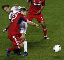 Chicago Fire's Logan Pause (12) and Real Salt Lake's Ned Grabavoy (20) hit in midfield during the second half of an MLS soccer game on Wednesday, May 9, 2012, at Toyota Park in Bridgeview, Ill. The game ended in a 0-0 tie. (AP Photo/John Smierciak)