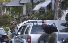 Jeremy Harmon  |  The Salt Lake Tribune  Salt Lake City SWAT team members stand outside a home at 1225 S. Windsor during a standoff with a man who had taken a woman hostage Thursday, May 10, 2012.