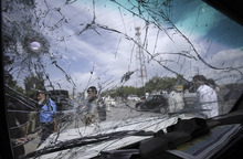 Pakistani police officers are seen through the shattered windshield of a vehicle at the site of a blast in Peshawar, Pakistan, Friday, May 11, 2012. An improvised explosive device (IED) planted inside a manhole, went off on a road in Peshawar on Friday, causing no casualties or injuries. (AP Photo/Mohammad Sajjad)