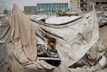 An Afghan child looks at UN Humanitarian chief Valerie Amos, unseen, during her visit to an informal settlement in Kabul, Afghanistan, Wednesday, May 9, 2012. Afghanistan's security situation has overshadowed the glaring humanitarian needs of the country's poorest, a top UN official said Wednesday, and the situation may worsen as international aid dwindles in the years ahead. (AP Photo/Musadeq Sadeq)