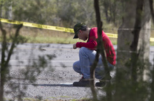 A forensic agent inspect the area where dozens of bodies, some of them mutilated, were dumped on a highway connecting the northern Mexican metropolis of Monterrey to the U.S. border,  in the town of San Juan, near the city of Monterrey, Mexico,  Sunday, May 13, 2012. (AP Photo/Christian Palma)