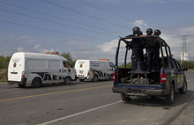 Federal police on a vehicle guard two of the three forensic trucks where several bodies were placed after dozens of bodies, some of them mutilated, were found on a highway connecting the northern Mexican metropolis of Monterrey to the U.S. border found in the Km 47 of the Reynosa-Cadereyta road in the town of San Juan near the city of Monterrey, Mexico,  Sunday, May 13, 2012. (AP Photo/Christian Palma)