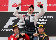 Williams's Pastor Maldonado, from Venezuela, centre, celebrates his victory lifted  by Ferrari's Fernando Alonso, from Spain, and Lotus's Kimi Raikkonen, from Finland, right after the Grand Prix of Spain  at Montmelo, racetrack  near Barcelona, Spain, Sunday, May 13, 2012. (AP Photo/Andres Kudacki)