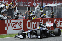 Williams Formula One driver, Pastor Maldonado, from Venezuela, drivers his car and celebrates beside his team mechanics after winning the Spanish Grand Prix at the Montmelo racetrack near Barcelona, Sunday May 13, 2012. (AP Photo/Alvaro Barrientos)
