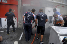 Williams team mechanics try to put out the fire inside of one garage of their team at the end of the Spanish Grand Prix at the Montmelo racetrack near Barcelona, Sunday May 13, 2012. Maldonado won the race. (AP Photo/Alvaro Barrientos)