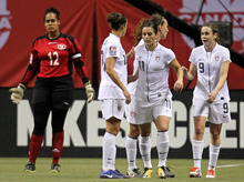 United States' Heather O'Reilly (9) celebrates her goal with teammates Alexandra Krieger (11) and Carli Lloyd (10) as Dominican Republic goalkeeper Heidy Salazar (12) looks on during the first half of a CONCACAF women's Olympic qualifying soccer match in Vancouver, British Columbia, Friday, Jan. 20, 2012.  (AP Photo/The Canadian Press, Jonathan Hayward)