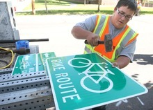 Rick Egan  | The Salt Lake Tribune  Salt Lake County sign specialist Orrey Nell prepares a bike route sign for Mayor Peter Corroon to install Monday on Evergreen Avenue in East Millcreek. The installation of bike route signs is part of Salt Lake County's new County Connectivity Project, which links major routes and popular destinations.