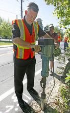 Rick Egan  | The Salt Lake Tribune  Salt Lake County Mayor Peter Corroon prepares to install a bike route sign on Evergreen Avenue Monday. Developing designated bike routes will help residents to reap the health and clean-air benefits of biking, and just