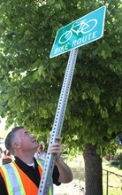 Rick Egan  |  The Salt Lake Tribune  Salt Lake County Mayor Peter Corroon prepares to install a bike route sign on Evergreen Avenue on Monday to raise awareness about Salt Lake County's new connectivity project.