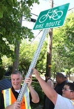 Rick Egan  | The Salt Lake Tribune  Salt Lake County Mayor Peter Corroon prepares to install a bike route sign with the help of sign specialist Orrey Nell on Evergreen Avenue.
