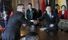 Al Hartmann  |  The Salt Lake Tribune Spencer P. Eccles Jr., executive director of the Governor's Office of Economic Development, left, reaches across table at the state Capitol to shake hands with Deng Yuyang, a representative of Chinese sculpture artist Yuan Xikun in thanks for  a three-generation statue of Chinese railroad workers. About 2,600 Chinese laborers worked on the transcontinental railroad completed 143 years ago at Promontory  Summit, near Brigahm City.