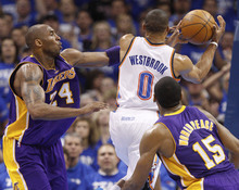 Los Angeles Lakers guard Kobe Bryant, left, fouls Oklahoma City Thunder guard Russell Westbrook (0) as Westbrook shoots between Bryant and forward Metta World Peace (15) during the second quarter in Game 2 of an NBA basketball playoffs Western Conference semifinal, in Oklahoma City on Wednesday, May 16, 2012. (AP Photo/Sue Ogrocki)