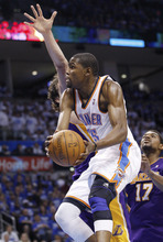 Oklahoma City Thunder forward Kevin Durant, front, shoots next to Los Angeles Lakers forward Pau Gasol, rear, and center Andrew Bynum (17) during the third quarter in Game 2 of an NBA basketball playoffs Western Conference semifinal, in Oklahoma City on Wednesday, May 16, 2012. (AP Photo/Sue Ogrocki)