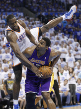 Oklahoma City Thunder forward Serge Ibaka, left, tumbles over Los Angeles Lakers center Andrew Bynum during the first quarter of Game 2 in an NBA basketball playoffs Western Conference semifinal, in Oklahoma City on Wednesday, May 16, 2012. (AP Photo/Sue Ogrocki)