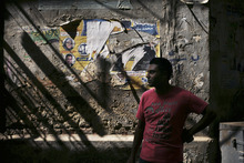 A man stands in front of defaced posters of candidates of the last parliamentary elections in Cairo, Egypt, Thursday, May 17, 2012. Egypt's first real competitive presidential race, with 13 candidates vying for the country's top job, starts May 23-24. (AP Photo/Manu Brabo)