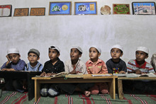 Pakistani boys listen to their teacher, not pictured, while attending their madrassa, or Islamic school, in a mosque in Islamabad, Pakistan, Thursday, May 17, 2012. (AP Photo/Muhammed Muheisen)