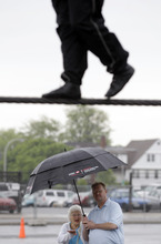 Nik Wallenda performs a walk on a tightrope in the rain as people watch during training for his walk over Niagara Falls in Niagara Falls, N.Y., Wednesday, May 16, 2012. (AP Photo/David Duprey)