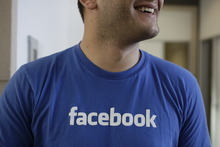 FILE - This Feb. 8, 2012 file photo shows a Facebook worker smiling inside Facebook headquarters in Menlo Park, Calif.  Facebook says 25 percent more shares will be sold as investors clamor for a piece of the year's hottest stock offering. Facebook said in a regulatory filing Wednesday, May 16, 2012 that about 421 million shares will be sold, up from 337 million under its earlier plans. The news comes a day after Facebook raised the expected price range for the stock to a range of $34 to $38 per share, up from $28 to $35.  (AP Photo/Paul Sakuma, File)