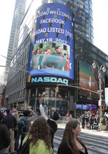 People in New York's Times Square watch Nasdaq's giant monitor as Facebook's stock begins trading on the Nasdaq stock market, Friday, May 18, 2012, in New York. (AP Photo/Bebeto Matthews)
