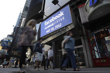 Passers-by walk near a sign for Facebook displayed at Nasdaq, Friday, May 18, 2012, in New York. The social media company priced its IPO on Thursday at $38 per share, and beginning Friday regular investors will have a chance to buy shares. (AP Photo/Richard Drew)