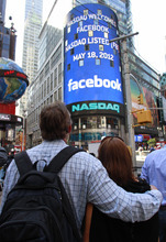 Matts and Maria Nedermam, tourists visiting from Sweden, view Nasdaq's giant monitor as it shows a welcome message for Facebook before the company began trading on the Nasdaq stock market, Friday, May 18, 2012, in New York.  (AP Photo/Bebeto Matthews)