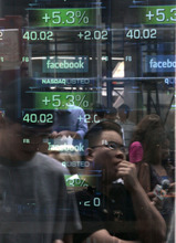 Passers-by are reflected in the window of the Nasdaq media center as they view reports of trading activity on Facebook's stock on the Nasdaq stock market on Friday, May 18, 2012, in New York. Facebook is trading up 8 percent as investors seek to put a dollar value on the company. (AP Photo/Bebeto Matthews)