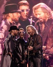 FILE - In this Dec. 31, 1999, file photo, The Bee Gees, from left, Maurice, Robin and Barry Gibb, perform in front of their projected images at the