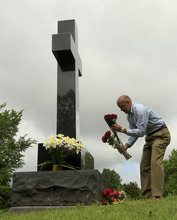 In this photo taken Monday, May 7, 2012, Mark Norton places flowers on the Webb City, Mo., grave of his son Will Norton, who died a year ago when he was sucked out of his car on the way home from his high school graduation by an EF-5 tornado that tore through Joplin, Mo. nearly a year ago. (AP Photo/Charlie Riedel)