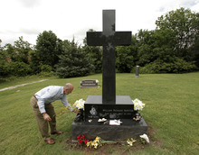 In this photo taken Monday, May 7, 2012, Mark Norton places flowers on the Webb City, Mo., grave of his son Will Norton, who died a year ago when he was sucked out of his car on the way home from his high school graduation by an EF-5 tornado that tore through Joplin, Mo., nearly a year ago. (AP Photo/Charlie Riedel)