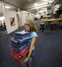 ** FILE ** In this Aug. 17, 2011 file photo, senior Holly O'Dell carries donated school supplies to a classroom on the first day of school at a temporary high school in a converted big-box store  in Joplin, Mo.  A year after the old high school and much of the rest of Joplin was destroyed by an EF-5 tornado on  graduation day, the community is preparing to graduate the class of 2012. (AP Photo/Charlie Riedel, File)