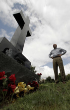 In this photo taken Monday, May 7, 2012, Mark Norton pauses at the Webb City, Mo., grave of his son Will Norton, who died a year ago when he was sucked out of his car on the way home from his high school graduation by an EF-5 tornado that tore through Joplin, Mo., nearly a year ago. (AP Photo/Charlie Riedel)