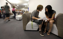 ** FILE ** In this Aug. 17, 2011 file photo, seniors Preston Colasanti and Lily Yang compare schedules on the first day of school at a temporary high school in a converted big-box store  in Joplin, Mo.  A year after the old high school and much of the rest of Joplin was destroyed by an EF-5 tornado on  graduation day, the community is preparing to graduate the class of 2012. (AP Photo/Charlie Riedel, File)