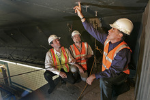 FILE - In this July 18, 2006, file photo, Gov. Mitt Romney, right, looks over bolts in the ceiling of a Big Dig tunnel while speaking with Alexander Bardow, center, Massachusetts Director of Bridges and Structures, and Massachusetts Secretary of Transportation John Cogliano in Boston. Romney was at his New Hampshire vacation home on a summer night in 2006 when tons of concrete ceiling panels in one of Boston's Big Dig highway tunnels collapsed. The debris crushed a car and killed a female passenger. Romney, then in his final year as Massachusetts governor, dashed back to Boston and immersed himself in the crisis. His response offers insights into what kind of leader the expected Republican nominee would be if elected president. Romney has made his management skills a major selling point in his campaign. (AP Photo/David L Ryan, Pool)