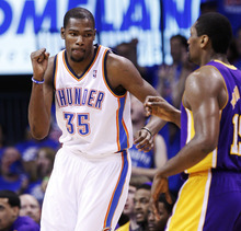 Oklahoma City Thunder forward Kevin Durant (35) pumps his fist in front of Los Angeles Lakers forward Metta World Peace, right, after hitting a basket in the third quarter of Game 5 in their NBA basketball Western Conference semifinal playoff series, Monday, May 21, 2012, in Oklahoma City. (AP Photo/Sue Ogrocki)