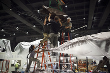 In a photo made May 15, 2012, paleontologists from the Black Hills Institute of Geologic Research with the help of film industry prop artists install a Tyrannosaurus Rex fossil skeleton in the new Hall of Paleontology at the Houston Museum of Natural Science Tuesday, May 15, 2012. The $85 million wing of the museum that opens June 2 will have the only Triceratops skin found to date and  a unique T-rex fossil with complete hands.  (AP Photo/Michael Stravato)