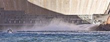 A Park Service boat approaches the base of the Glen Canyon Dam where water is surging into the Colorado River during a 2008 test flood. Paul Fraughton /The Salt Lake Tribune; 3/5/08