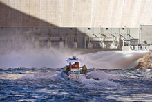 Tribune file photo A Park Service boat approaches the base of the Glen Canyon Dam in 2008 as water surged into the Colorado River. U.S. Interior Secretary Ken Salazar announced Wednesday that the government will routinely crank up flows out of Glen Canyon Dam whenever spring or fall rains create conditions likely to maximize sediment flows into the Grand Canyon.
