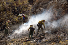 Jud Burkett  | The Spectrum Forest Service firefighters work on extinguishing hot spots Wednesday from a wildfire that burned through the cliffs east of Hurricane.