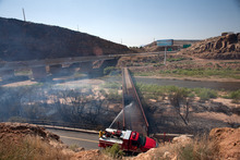 Jud Burkett | The Spectrum  St. George Fire Department firefighters work Wednesday on trying to extinguish the flames burning a foot bridge over the Virgin River after a wildfire swept through the area.