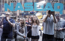 Richard Drew  |  The Associated Press Curious bystanders watch through the Nasdaq windows as Facebook shares begin trading on May 18 in New York. On Wednesday, shares regained some ground, rising $1, or 3.2 percent, to close at $32.