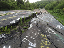 Michael Rubinkam  |  The Associated Press On May 24, 2012, Route 61 is shown eroded and covered in graffiti in Centralia, Pa. Fifty years ago on May 27, a fire at the town dump spread to a network of coal mines underneath hundreds of homes and business in the northeastern Pennsylvania borough of Centralia, eventually forcing the demolition of nearly every building.