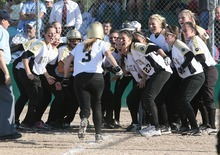 Paul Fraughton / Salt Lake Tribune Roy's Bryce Mitchell is greeted at home plate by her teammates after hitting a three run homer to give Roy High the lead in their championship game against Salem Hills.    Thursday, May 24, 2012